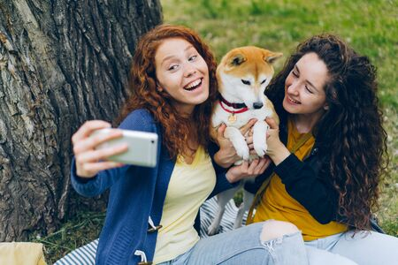 Attractive young ladies taking selfie with small dog in park posing for smartphone camera smiling having fun. People, technology and photograph concept. Imagens
