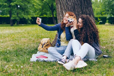 Female students joyful girls taking selfie with adorable puppy in park using smartphone camera having fun together. People, youth and animals concept. Imagens