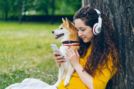 Beautiful girl hipster is using smartphone and listening to music in headphones sitting with dog in park relaxing. People, leisure and domestic animals concept. Imagens