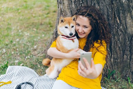 Portrait of happy young girl taking selfie with adorable dog in park hugging lovely pet holding camera smiling enjoying friendship with puppy. Youth and lifestyle concept.
