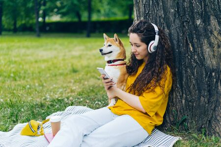 Beautiful young woman is using smartphone and listening to music in wireless headphones in green summer park with dog. Leisure time and animals concept.