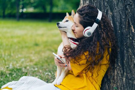 Happy lady in headphones is listening to music using modern smartphone and hugging shiba inu pet dog in green park. Technology, people and animals concept. Imagens