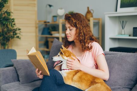 Pretty woman is reading interesting book smiling and stroking shiba inu puppy sitting on sofa at home. Youth culture, lifestyle and domestic animals concept. Banco de Imagens