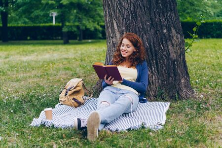 Beautiful young woman is reading book sitting on blanket under tree in park and smiling enjoying summertime and literature. People and lifestyle concept.