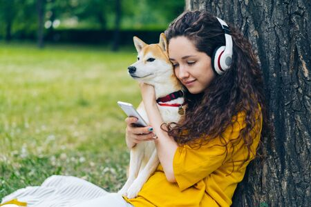 Smiling student attractive girl is enjoying pop music in headphones using smartphone sitting on lawn in park with beautiful shiba inu dog. People and pets concept. Imagens