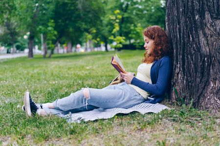 Cheerful redhead girl reading book outdoors in park smiling relaxing sitting on grass alone enjoying story and nature. People, lifestyle and summer concept. Imagens