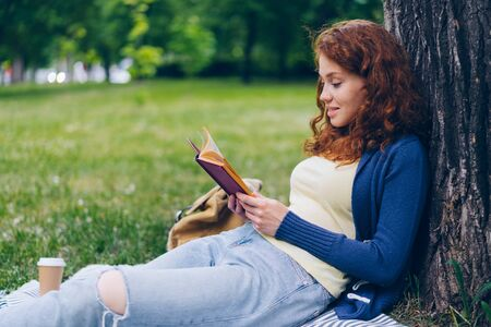 Good-looking young lady reading book and smiling sitting on lawn in park on beautiful summer day relaxing in recreational area. People, hobby and culture concept.
