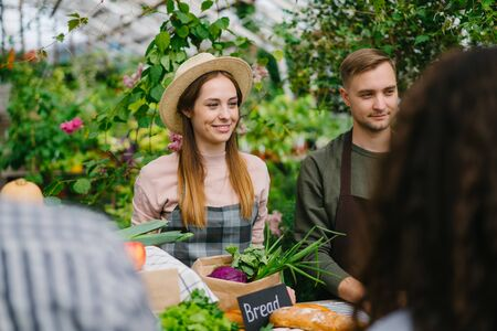 Young farmers man and woman are selling organic vegetables to consumers in greenhouse market smiling. Small business, nature and happy people concept. Stock fotó