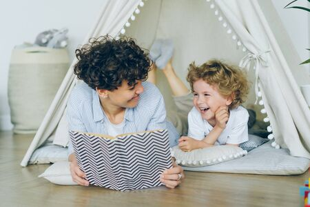 Loving mother is reading interesting book to cute child lying on floor in cosy tent indoors in modern light apartment smiling speaking. People and childhood concept. Фото со стока