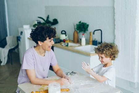 Mother and little son are having fun with flour cooking home-made cookies in kitchen enjoying joyful activity together. Lifestyle, relationship and people concept.