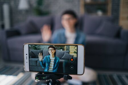 Joyful girl recording video with smartphone camera talking waving hand at home, focus on mobile screen. Blogging, modern devices and happy youth concept.