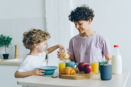 Happy young family mother and little son eating cereal with milk at home talking enjoying domestic breakfast in cosy kitchen. People and meals concept.