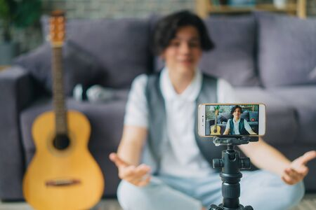 Portrait of teenage boy using smartphone to record video for internet vlog talking gesturing in modern apartment. People, devices and lifestyle concept.