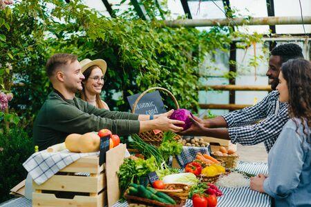Un couple d'agriculteurs, homme et femme, vend du chou aux clients au marché agricole en serre donnant des légumes souriants. Concept commercial et commercial.