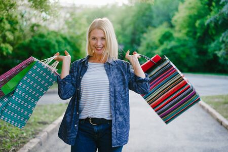 Portrait of happy woman shopaholic standing outdoors with shopping bags smiling enjoying day in city park. Consumerism, happiness and lifestyle concept.