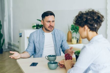Annoyed man husband is yelling at unhappy wife in kitchen fighting gesturing sitting at table together shouting at each other. Conflict, problems and family concept.