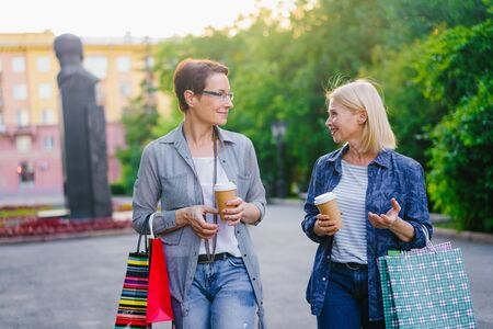 Joyful friends mature women are walking in street holding to go coffee and bright paper shopping bags talking enjoying conversation. Lifestyle and friendship concept.