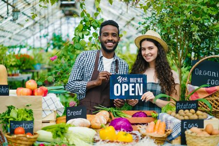 Man and woman in aprons are holding open sign standing at table with organic food in greenhouse market smiling looking at camera welcoming customers.