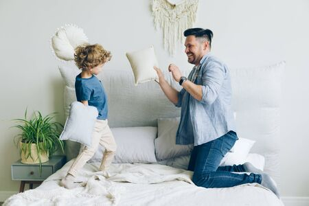 Young man loving father is fighting pillows with little son having fun on bed in apartment enjoying game with small child. Lifestyle, fatherhood and people concept.