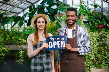 Homme et femme heureux partenaires d'affaires tiennent nous sommes signe ouvert en serre souriant regardant la caméra invitant les gens à manger des aliments biologiques et des fleurs.