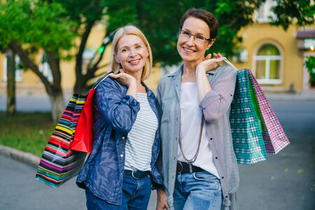 Portrait of beautiful mature ladies friends holding shopping bags looking at camera smiling outdoors in city street. People, friendship and consumerism concept.