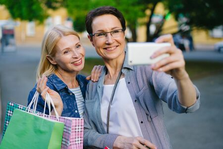 Female friends blonde and brunette taking selfie with shopping bags outside using modern smartphone posing smiling. People, emotions and consumerism concept.