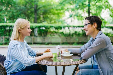 Mature lady is talking to female friend in open air cafe having fun smiling sitting at table together. Conversation, people and modern lifestyle concept. Banco de Imagens