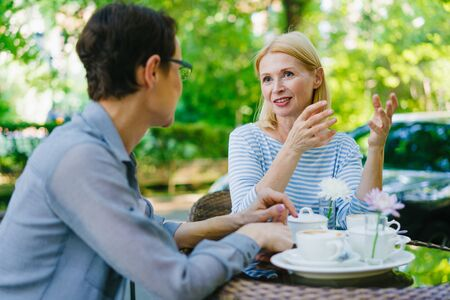Happy mature women are chatting in outdoor cafe relaxing at table enjoying company on warm summer day. Modern lifestyle, friendship and happiness concept.