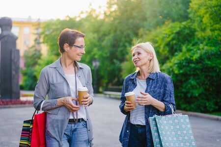 Portrait of beautiful mature women chatting holding shopping bags and coffee walking outside in park. People, modern lifestyle and consumerism concept. 免版税图像