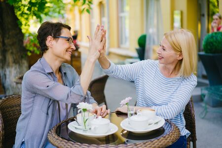 Happy mature women friends are doing high-five and laughing sitting in outdoor cafe in summer. Friendship, cheerful people and modern lifestyle concept. Zdjęcie Seryjne