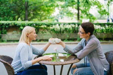 Mature women friends are celebrating meeting clinking tea cups in outdoor cafe smiling talking together. Friendship, modern lifestyle and happiness concept. 免版税图像