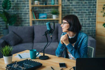 La giovane donna seria in vetri sta parlando nel discorso di registrazione del microfono per l'audio blog a casa. Tecnologia moderna, millennial e concetto di occupazione. Archivio Fotografico