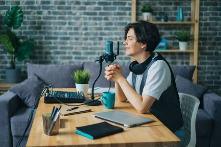 Good-looking teenager speaking in microphone in sound recording studio sitting at desk alone using modern equipment. Audio podcasts and adolescence concept. 免版税图像