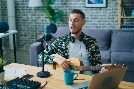 Blogger handsome young man is playing the guitar and singing recording music in modern studio using microphone, laptop and sound mixer. People and blogging concept.