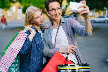 Attractive mature ladies are using smartphone outdoors taking selfie with shopping bags posing smiling having fun. Technology, consumerism and people concept.