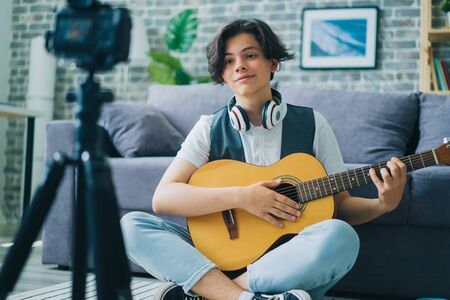 Teenage musician young boy is recording video holding guitar using modern camera in apartment. Musical instruments, childhood and occupation concept.