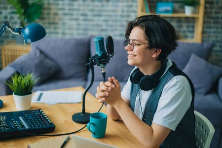 Joyful teen is speaking in microphone in studio audio recording podcast alone using modern equipment. Youth, communication and professional blogging concept. Zdjęcie Seryjne