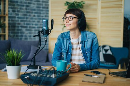 Beautiful young woman blogger in headphones is recording podcast using microphone sitting at table at home. Blogging, lifestyle and audio records concept. Zdjęcie Seryjne