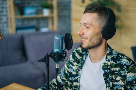 Happy young man in headphones is busy talking in microphone in recording studio smiling enjoying communication. Podcasts and audio blogging concept.