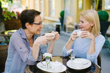 Mature ladies friends are drinking coffee and talking sitting in open air cafe on summer day enjoying drinks and conversation. People and relaxation concept.