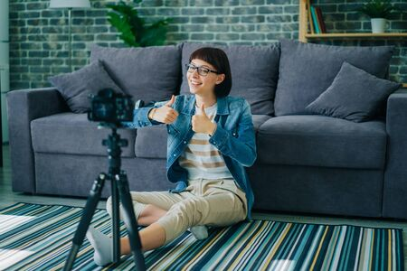 Portrait of successful female blogger recording video with modern camera showing thumbs-up sitting on floor at home. Blogging, youth and apartment concept.