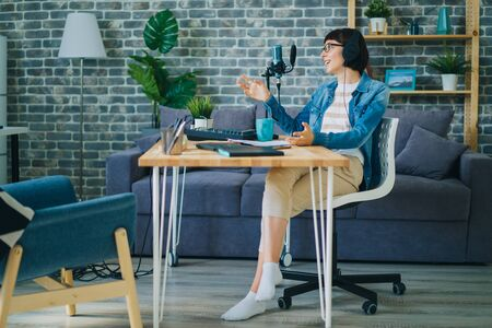Cheerful young lady in glasses is talking recording audio using microphone in apartment enjoying communication and blogging activity. Youth culture and devices concept. 免版税图像
