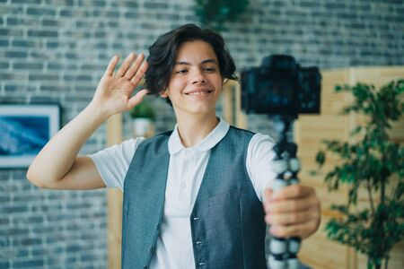 Creative student stylish boy is recording video holding camera talking gesturing at home in loft style room. Blogging, apartment and young people concept. 免版税图像