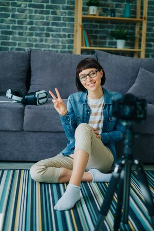 Cheerful woman in glasses is smiling and showing v-sign recording video at home for online blog sitting on floor in house . Youth, technology and apartment concept.