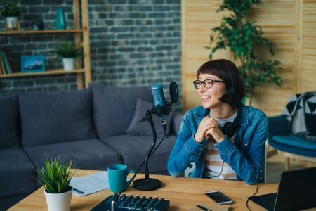 Happy girl blogger is speaking in microphone in recording studio smiling creating podcast for internet blog. Occupation, blogging and youth concept.