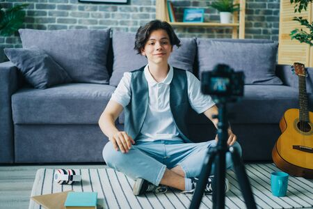 Creative boy vlogger is recording video for online vlog speaking gesturing sitting on floor at home. Vlogging, modern technology and youth lifestyle concept.