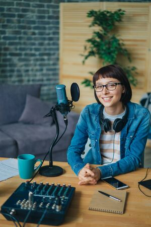 Portrait of beautiful young lady blogger sitting at table in recording studio smiling looking at camera, modern equipment visible on desk. Youth and blogging concept.