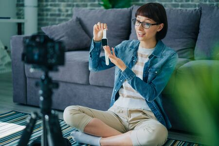 Good-looking woman holding watch recording video about gadget speaking for camera giving advice to followers. Youth, blogging and devices concept.
