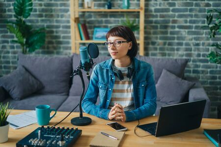 Portrait of young adult woman recording podcast for audio blog using mic, headphones and laptop working at table at home. Blogging, equipment and apartment concept.