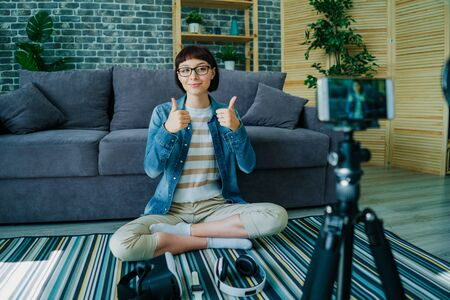 Pretty young lady blogger recording video with smartphone showing thumbs-up sitting on floor at home. Blogging, creative youth and apartment concept.